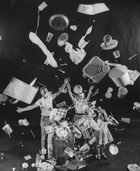 Three children tossing paper cups, plates, aluminum foil pans, lunch trays, straws and napkins through the air illustrating the usefulness of disposable dishes. A photo from Life Magazine's 1955 story titled, Throwaway Living: Dozens of Disposable Housewares Eliminate the Chore of Cleaning Up. Photo via Time Magazine.