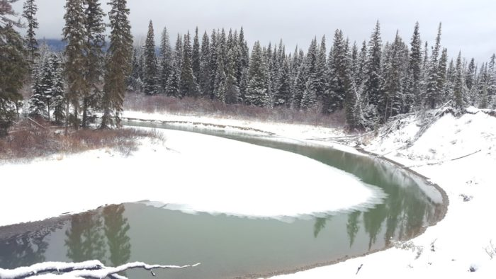 A teal, reflective river bends within a snowy coniferous forest