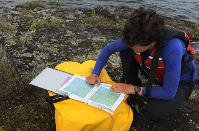 A person wearing a life jacket crouches on the edge of a lake, reading a map